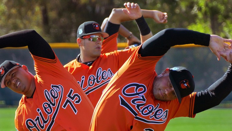 Baltimore Orioles players (from left) catchers Yermin Mercedes (75), Francisco Pena, and Welington Castillo stretch while standing in line during spring training at the Ed Smith Stadium baseball complex. (Karl Merton Ferron / Baltimore Sun)