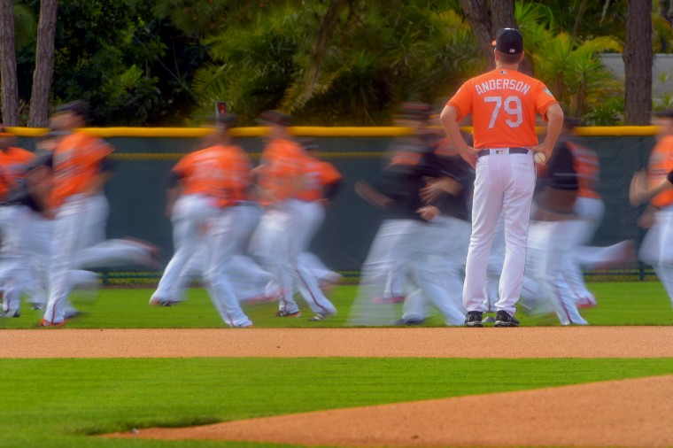 Baltimore Orioles support staff Dave Anderson stands, watching the pitchers rush in front of him as they loosen for the day's activities and drills during spring training at the Ed Smith Stadium baseball complex. (Karl Merton Ferron / Baltimore Sun)