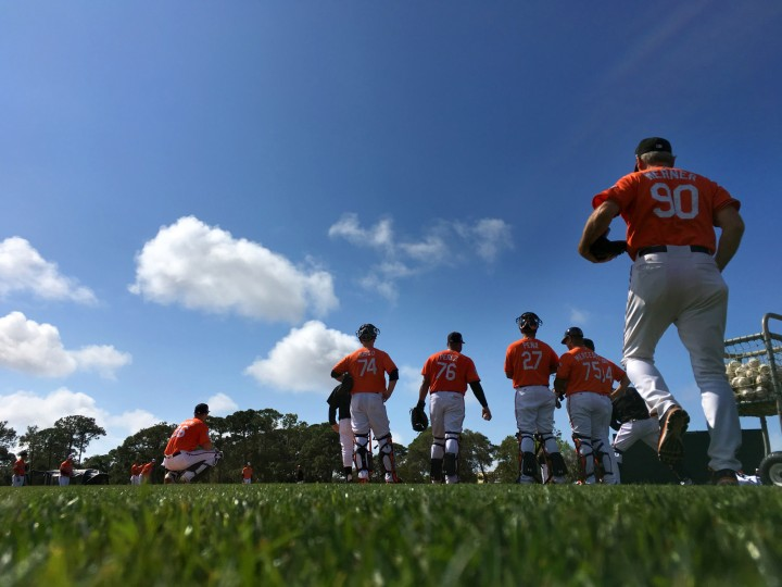 Coach Don Werner (90) watches Baltimore Orioles catchers participate in fielding drills during spring training at the Ed Smith Stadium baseball complex. (Karl Merton Ferron / Baltimore Sun)