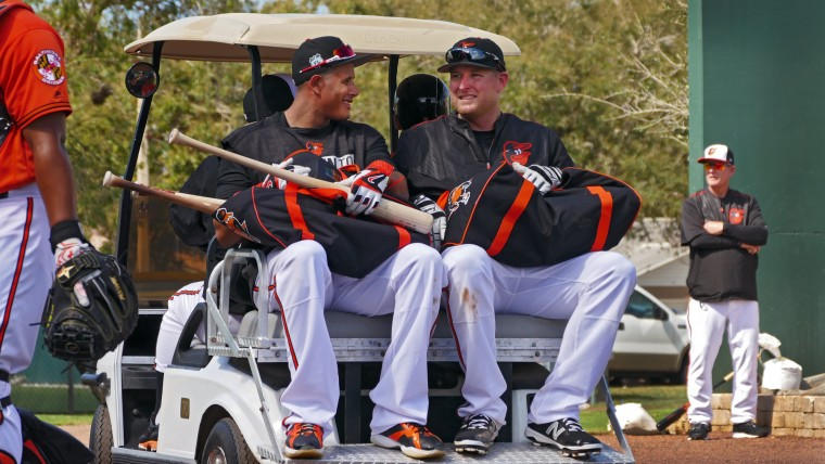 Baltimore Orioles' Manny Machado (left) smiles while talking with  Mark Trumbo as they and third baseman Ryan Flaherty (front) get a ride from the batting cages to the practice fields with manager Buck Showalter during spring training at the Ed Smith Stadium baseball complex. (Karl Merton Ferron / Baltimore Sun)