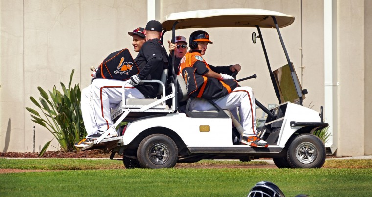 Baltimore Orioles' Manny Machado (left, back) smiles while talking with  Mark Trumbo as they and third baseman Ryan Flaherty (front right) get a ride from the batting cages to the practice fields with manager Buck Showalter during spring training at the Ed Smith Stadium baseball complex. (Karl Merton Ferron / Baltimore Sun)
