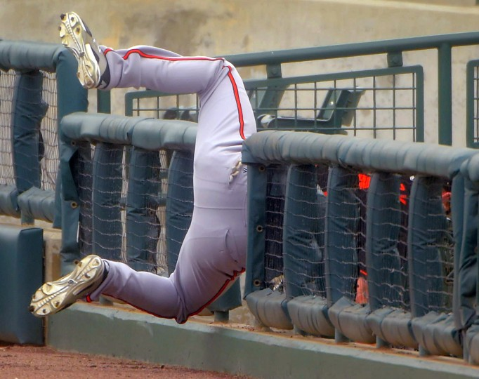 Baltimore Orioles outfielder Chad Gentry (14) hustles on the warning track to catch a foul ball before tumbling over the short right field fence  during the team's first intrasquad game at Ed Smith Stadium baseball complex. (Karl Merton Ferron / Baltimore Sun)