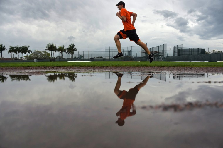 In his first day at the complex since being acquired from the New York Yankees, Baltimore Orioles pitcher Richard Bleier runs behind a pool of standing water on a rain-filled morning that shortened camp for the day, during spring training at the Ed Smith Stadium baseball complex. (Karl Merton Ferron / Baltimore Sun)