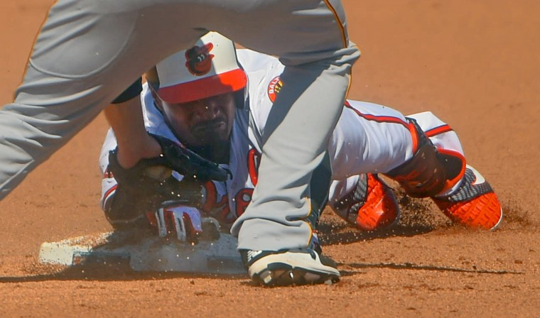 Baltimore Orioles' Adam Jones grimaces among the gravel, sliding safely under the tag of Pittsburgh Pirates second baseman Phil Gosselin during the Orioles' inaugural spring training home opener at Ed Smith Stadium. (Karl Merton Ferron / Baltimore Sun)