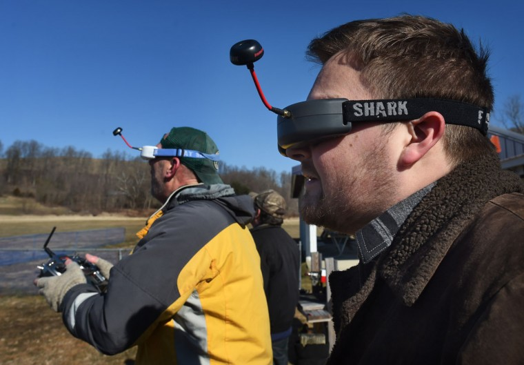 Joseph Brackins, right, uses FPV goggle to see what a camera mounted on a RC plane shows in real time. The RC plant is flown by Drew Wilkerson, left, who is also using a FPV goggle while flying the model plane via radio control unit. (Kenneth K. Lam/Baltimore Sun)