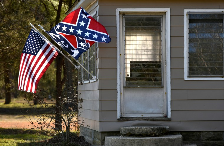 A confederate flag is displayed alongside a US flag at a home on Greensboro Road.  (Amy Davis/Baltimore Sun)