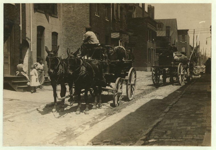 Waiting for the human cargo to start for the Maryland berry fields. Taken on Fells Point, Baltimore, Md. Courtesy of Maryland Child Labor [Comm]ittee. Location: Baltimore, Maryland. 1910 May. (Lewis Hine/Photo courtesy LOC)