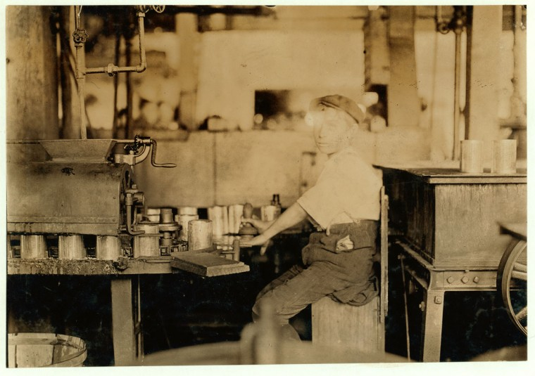 Dangerous Business. Boy working at canning machine with open gearing. Many suck machines and boys too. J. S. Farrand Packing Co. Witness--J. W. Magruder. July 7, 1909. Location: Baltimore, Maryland. (Lewis Hine/Photo courtesy LOC)