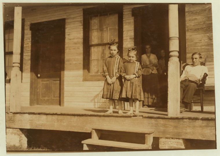 Bessie, four years old, and Marietta, seven years old, both shuck oysters in Barataria Canning Company. Mother is Mrs. Ida Thompson, Baltimore. Location: Biloxi, Mississippi. 1911 February. (Lewis Hine/Photo courtesy LOC)