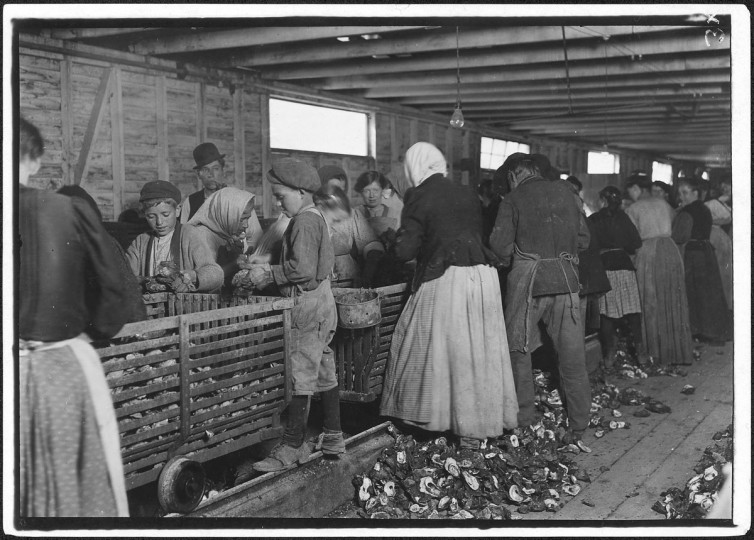 Original Caption: Johnnie, a nine year old oyster shucker. Man with pipe is a padrone who has brought these people from Baltimore for four years. He said, I tell you I have to lie to 'em. They're never satisfied. Hard work to get them. He is the boss of the shucking shed. Dunbar, La, March 1911. (Lewis Hine/Photo courtesy of NARA)