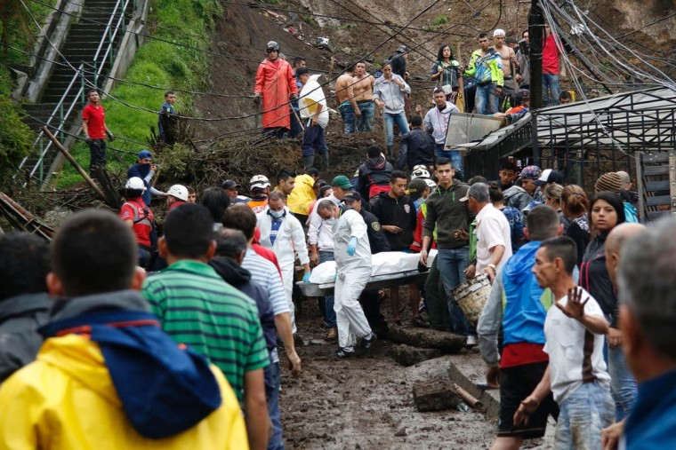 Rescuers carry a corpse after mudslides in Manizales, Caldas department, Colombia on April 19, 2017. Flooding and mudslides in central Colombia have killed at least eleven people, the Red Cross said Wednesday, causing alarm in a country still recovering from mudslides that killed hundreds. (Getty Images)
