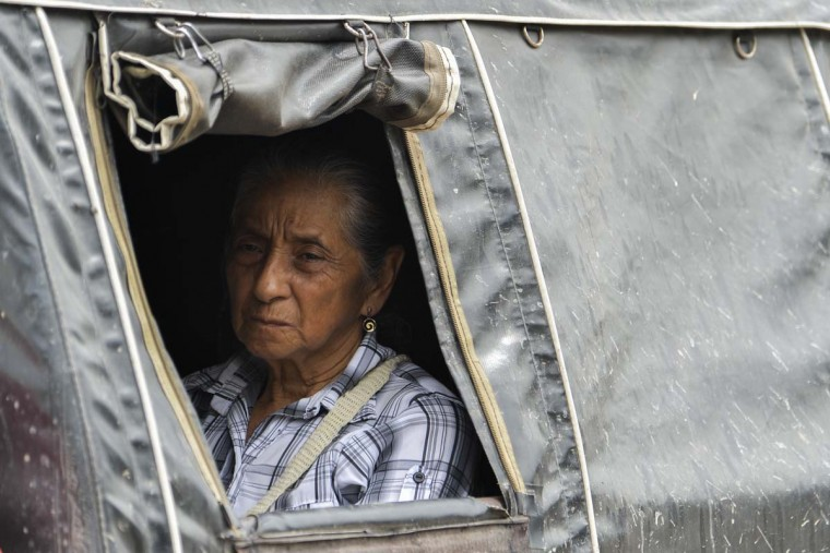 A woman sits on a public transport vehicle on April 5, 2017 as she waits to leave Mocoa, Putumayo department, southern Colombia, affected by mudslides caused by heavy rains. A state of economic emergency has been declared in the town of Mocoa in southern Colombia, after mudslides left more than 290 people dead. And local officials urged the government to dispatch more police and troops to secure the region and prevent the looting of abandoned homes, while some residents have decided to leave for a while for fear of epidemics that could be caused by the natural disaster. (LUIS ROBAYO/AFP/Getty Images)