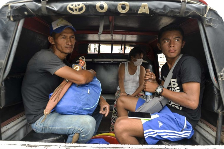 People wait in a public transport vehicle on April 5, 2017 to leave Mocoa, Putumayo department, southern Colombia, affected by mudslides caused by heavy rains. A state of economic emergency has been declared in the town of Mocoa in southern Colombia, after mudslides left more than 290 people dead. And local officials urged the government to dispatch more police and troops to secure the region and prevent the looting of abandoned homes, while some residents have decided to leave for a while for fear of epidemics that could be caused by the natural disaster. (LUIS ROBAYO/AFP/Getty Images)