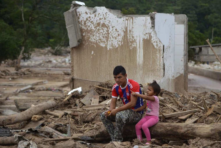 "A man and his daughter remain amid rubble in Mocoa, Putumayo department, Colombia on April 4, 2017. Meanwhile, looting has become a problem in some areas. Local officials urged the government to dispatch more police and troops to secure the region and prevent the looting of abandoned homes. ""What the mudslides didn't carry away, the thieves did,"" one survivor of the disaster, Juan Luis Hernandez, 33, told AFP in the devastated San Miguel neighborhood of Mocoa. (LUIS ROBAYO/AFP/Getty Images)"