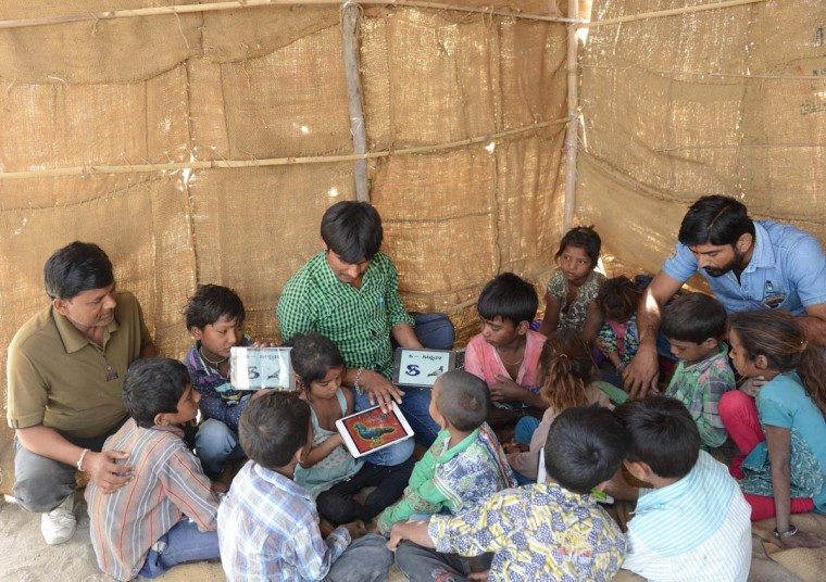 This picture taken on April 7, 2017 shows Indian teacher Deepsinh Vanol (right), Anand Solanki (center), facilitator of the 'Zero Connect' programme, and Bharatbhai Somera (left), district co-ordinator of the Agariya Heet Rakshak Manch, with a group of children of salt pan workers during a tent school workshop using an Internet-connected van, in the Little Rann of Kutch (LRK) region of Gujarat some 180km west of Ahmedabad. The children of Indian salt pan workers, drawn from the Agariya community in Gujarat state, accompany their parents in the remote and arid Little Rann of Kutch (LRK) region for nearly eight months of the year during the salt farming season. The 'Zero Connect' initiative provides basic education for the children in a joint initiative by the Agaria Heet Rakshak Manch, Digital Empowerment Foundation, Internet Society and Wireless for Communities groups. The initiative runs mobile workshops for the children, providing online access and education materials. (SAM PANTHAKY/AFP/Getty Images)