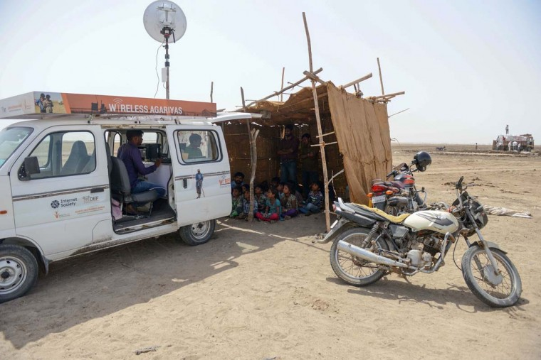 This picture taken on April 7, 2017 shows a group of children of salt pan workers at a tent school workshop next to an Internet-connected van provided by the 'Zero Connect' programme in the Little Rann of Kutch (LRK) region of Gujarat some 180km west of Ahmedabad. The children of Indian salt pan workers, drawn from the Agariya community in Gujarat state, accompany their parents in the remote and arid Little Rann of Kutch (LRK) region for nearly eight months of the year during the salt farming season. The 'Zero Connect' initiative provides basic education for the children in a joint initiative by the Agaria Heet Rakshak Manch, Digital Empowerment Foundation, Internet Society and Wireless for Communities groups. The initiative runs mobile workshops for the children, providing online access and education materials. (SAM PANTHAKY/AFP/Getty Images)