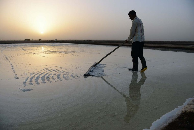 This picture taken on April 7, 2017 shows Indian salt pan worker Nirmalbhai Jakhodia working in the Little Rann of Kutch (LRK) region of Gujarat some 180km west of Ahmedabad. Indian salt pan workers of the Agariya community in Gujarat work in the remote and arid Little Rann of Kutch (LRK) region for nearly eight months of the year during the salt farming season. India is ranked third in gross amount of salt produced in the world, behind China and the United States, and the western state of Gujarat accounts for 77 percent of India's production. (SAM PANTHAKY/AFP/Getty Images)