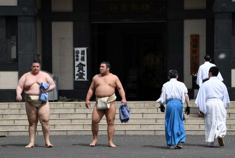 Sumo wrestlers walk in a compound of Yasukuni Shrine in Tokyo on April 17, 2017. Sumo's top wrestlers took part in an annual one-day exhibition for thousands of spectators within the shrine's precincts. (TOSHIFUMI KITAMURA/AFP/Getty Images)
