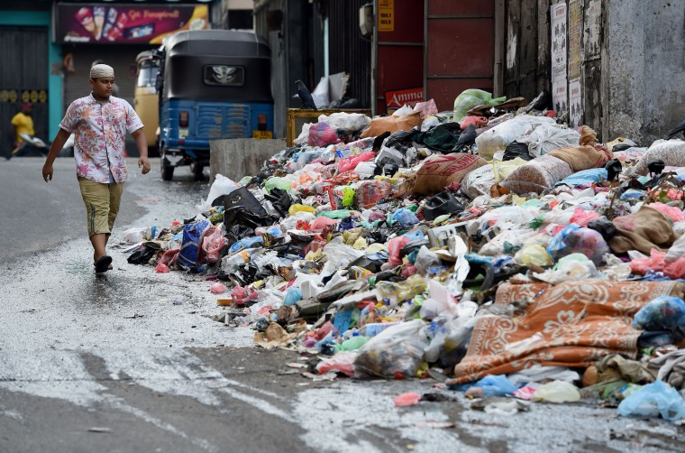 A Sri Lankan child walks by piles of garbage on a street in Colombo on April 18, 2017. Hundreds of tonnes of rotting garbage piled up in Sri Lanka's capital on April 18 after the main rubbish dump was shut following an accident that killed at least 30 people. (Ishara S. Kodikara/AFP/Getty Images)
