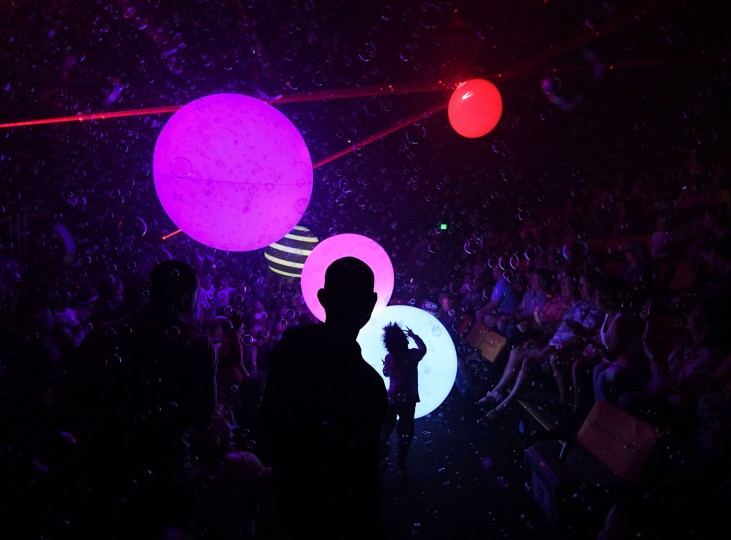 Children play as bubble artist Deni Yang performs his act during his Mega Bubblefest Laser Show at the Discovery Cube Science Center in Santa Ana, California on April 6, 2017. Deni, who is the son of famed bubble master Fan Yang, has followed in his father's footsteps and travels the world performing his bubble shows. His family holds the world record for largest soap bubble, measuring 167 feet long, that was created in Beijing, China in 2009. (Mark Ralston/AFP/Getty Images)