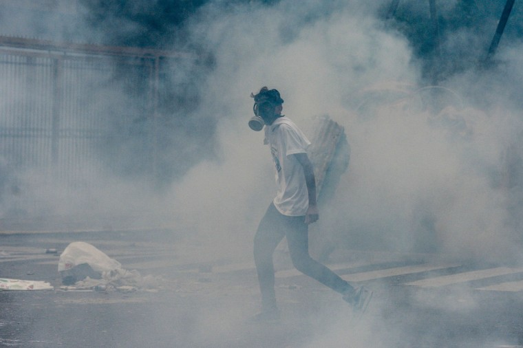 A demonstrator wearing a gas mask walks engulfed in a cloud of tear gas fired by riot police during an opposition march against Venezuelan President Nicolas Maduro, in Caracas on April 19, 2017. Venezuelans took to the streets Wednesday for massive demonstrations for and against President Nicolas Maduro, whose push to tighten his grip on power has triggered deadly unrest that has escalated the country's political and economic crisis. (Federico Parra/AFP/Getty Images)