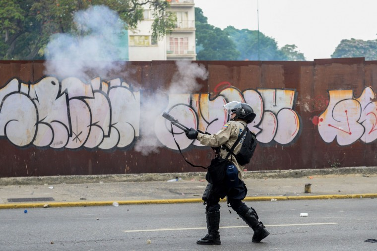 A policeman in riot gear fires tear gas at demonstrators during a march against Venezuelan President Nicolas Maduro, in Caracas on April 19, 2017. Venezuelans took to the streets Wednesday for massive demonstrations for and against President Nicolas Maduro, whose push to tighten his grip on power has triggered deadly unrest that has escalated the country's political and economic crisis. (Federico Parra/AFP/Getty Images)
