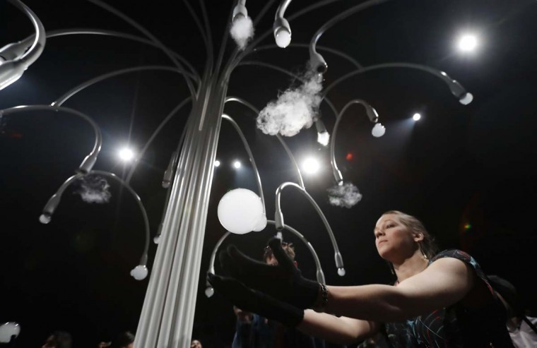 """A woman takes a ball as she visits an installation called """"New Spring"""" by Studio Swine for Cos' furniture designers, part of the Design Fair exhibition in Milan, Italy, Thursday, April 6, 2017. It is a multi-sensory installation. (AP Photo/Antonio Calanni)"""