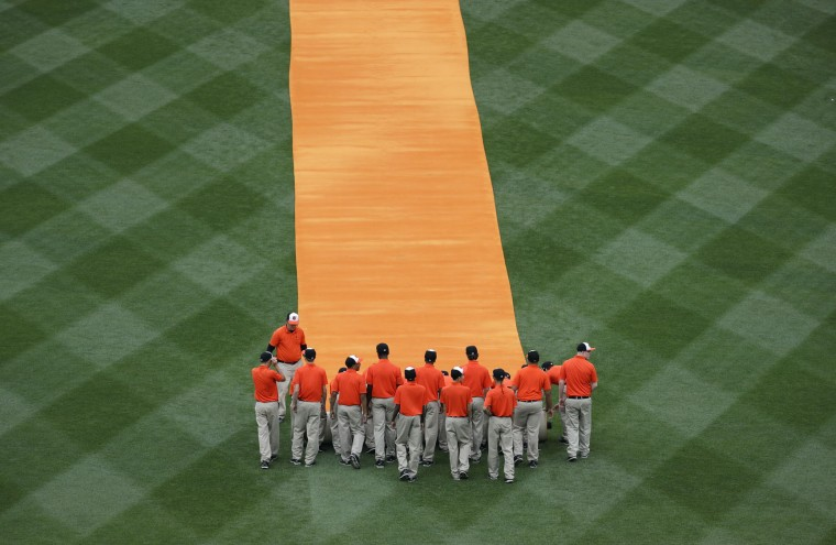 Groundskeepers roll up an orange carpet for members of the Baltimore Orioles after they were introduced before an opening day baseball game against the Toronto Blue Jays in Baltimore, Monday, April 3, 2017. (AP Photo/Patrick Semansky)