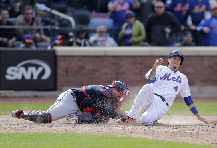 New York Mets Wilmer Flores (4), right, slides safely into home in front of Atlanta Braves catcher Tyler Flowers (25) during the seventh inning of an opening day baseball game at Citi Field, Monday, April 3, 2017, in New York. (AP Photo/Seth Wenig)