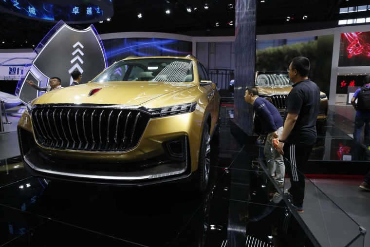 Visitors look at a car from Chinese automaker Hongqi during the Auto Shanghai 2017 show at the National Exhibition and Convention Center in Shanghai, China, Wednesday, April 19, 2017. Models on display at Auto Shanghai 2017, the global industry's biggest marketing event of the year, reflect the conflict between Beijing's ambitions to promote environmentally friendly propulsion and Chinese consumers' love of hulking, fuel-hungry SUVs. (AP Photo/Ng Han Guan)