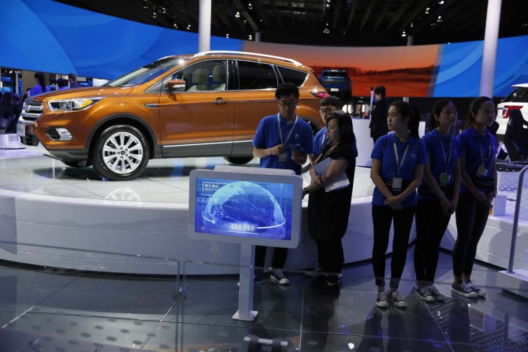 Workers wait for visitors to the Ford stand during the Auto Shanghai 2017 show at the National Exhibition and Convention Center in Shanghai, China, Wednesday, April 19, 2017. Models on display at Auto Shanghai 2017, the global industry's biggest marketing event of the year, reflect the conflict between Beijing's ambitions to promote environmentally friendly propulsion and Chinese consumers' love of hulking, fuel-hungry SUVs. (AP Photo/Ng Han Guan)