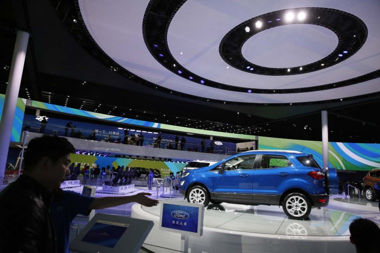 A worker guides visitor at the Ford stand during the Auto Shanghai 2017 show at the National Exhibition and Convention Center in Shanghai, China, Wednesday, April 19, 2017. Models on display at Auto Shanghai 2017, the global industry's biggest marketing event of the year, reflect the conflict between Beijing's ambitions to promote environmentally friendly propulsion and Chinese consumers' love of hulking, fuel-hungry SUVs. (AP Photo/Ng Han Guan)