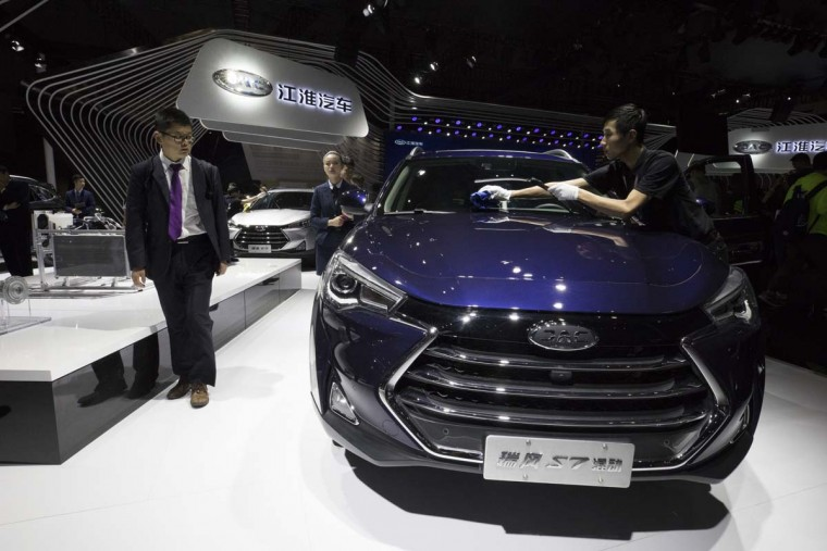 A worker cleans the S7 SUV from Chinese automaker JAC at the Auto Shanghai 2017 show at the National Exhibition and Convention Center in Shanghai, China, Wednesday, April 19, 2017. Models on display at Auto Shanghai 2017, the global industry's biggest marketing event of the year, reflect the conflict between Beijing's ambitions to promote environmentally friendly propulsion and Chinese consumers' love of hulking, fuel-hungry SUVs. (AP Photo/Ng Han Guan)