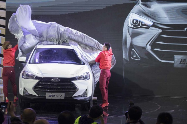 Performers unveil the S7 SUV from Chinese automaker JAC at the Auto Shanghai 2017 show at the National Exhibition and Convention Center in Shanghai, China, Wednesday, April 19, 2017. Models on display at Auto Shanghai 2017, the global industry's biggest marketing event of the year, reflect the conflict between Beijing's ambitions to promote environmentally friendly propulsion and Chinese consumers' love of hulking, fuel-hungry SUVs. (AP Photo/Ng Han Guan)