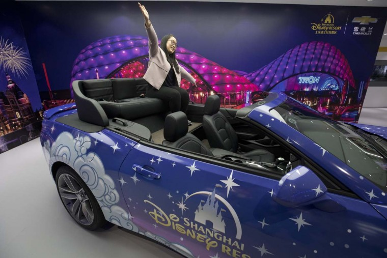A visitor poses for photos on a converted Chevrolet Camaro car in collaboration with Disney displayed at the Auto Shanghai 2017 show at the National Exhibition and Convention Center in Shanghai, China, Wednesday, April 19, 2017. Models on display at Auto Shanghai 2017, the global industry's biggest marketing event of the year, reflect the conflict between Beijing's ambitions to promote environmentally friendly propulsion and Chinese consumers' love of hulking, fuel-hungry SUVs. (AP Photo/Ng Han Guan)