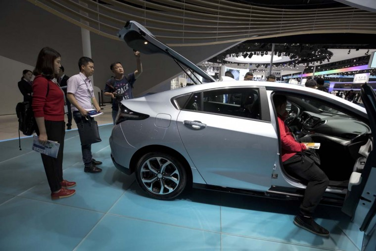 Visitors take a closer look at Buick's Velite 5, a rebranded Chevrolet Volt on display at the Auto Shanghai 2017 show at the National Exhibition and Convention Center in Shanghai, China, Wednesday, April 19, 2017. On Tuesday, General Motors Co. said it will produce the gasoline-electric hybrid version of its Chevrolet Volt in China. (AP Photo/Ng Han Guan)