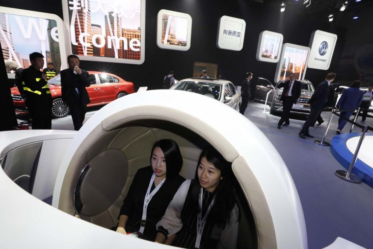 Visitors try out at a futuristic driver assistance system for cars at the Volkswagen stand at the Auto Shanghai 2017 show at the National Exhibition and Convention Center in Shanghai, China, Wednesday, April 19, 2017. Models on display at Auto Shanghai 2017, the global industry's biggest marketing event of the year, reflect the conflict between Beijing's ambitions to promote environmentally friendly propulsion and Chinese consumers' love of hulking, fuel-hungry SUVs. (AP Photo/Ng Han Guan)