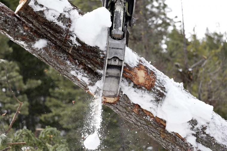 In this Feb. 22, 2017, photo, a log felled days earlier is grabbed by a log yarder after being hauled up a steep slope where a crew is thinning a 100-acre patch on private land owned by the Nature Conservancy overlooking Cle Elum Lake, in Cle Elum, Wash. As part of a broader plan by the nonprofit environmental group to restore the pine forests of the Central Cascades so they are more resilient to wildfires and climate change, they're cutting down trees to save the forest. (AP Photo/Elaine Thompson)