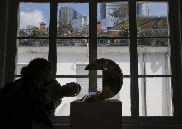 Visitors look at a lamp, a creation by Pierre Cardin, during his exhibition 'Les Cultures Utilitaires' at the Galleria Sozzani, part of the Design Fair exhibition in Milan, Italy, Wednesday, April 5, 2017. (AP Photo/Luca Bruno)
