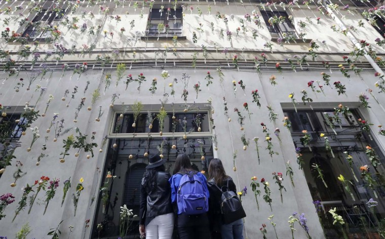 """People look at a creation by Piuarch called """"Flowerprint"""", part of the Design Fair exhibition in Milan, Italy, Tuesday, April 4, 2017. (AP Photo/Antonio Calanni)"""