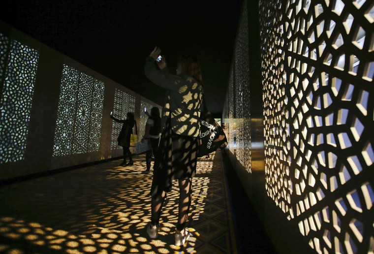 Visitors takes selfies at the entrance of the 'Corian Cabana Club' interior design and decorative art exhibition, part of the Design Fair exhibition, in Milan, Italy, Thursday, April 6, 2017. (AP Photo/Luca Bruno)