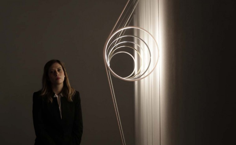 A woman stands next to creations by Flos' furniture designers, part of the Design Fair exhibition in Milan, Italy, Tuesday, April 4, 2017. (AP Photo/Antonio Calanni)