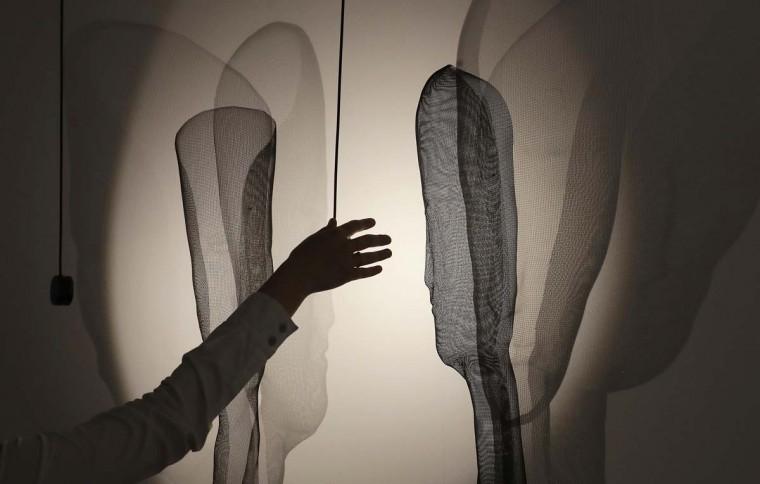 A woman tests a lamp created by Arturo Alvarez's furniture designers, part of the Design Fair exhibition in Milan, Italy, Tuesday, April 4, 2017. (AP Photo/Antonio Calanni)