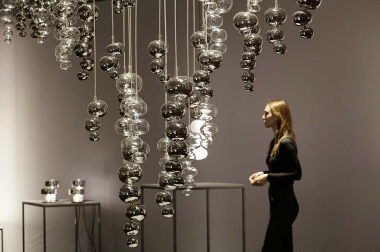 A woman walks past creations by Melogranoblu's furniture designers, part of the Design Fair exhibition in Milan, Italy, Tuesday, April 4, 2017. (AP Photo/Antonio Calanni)