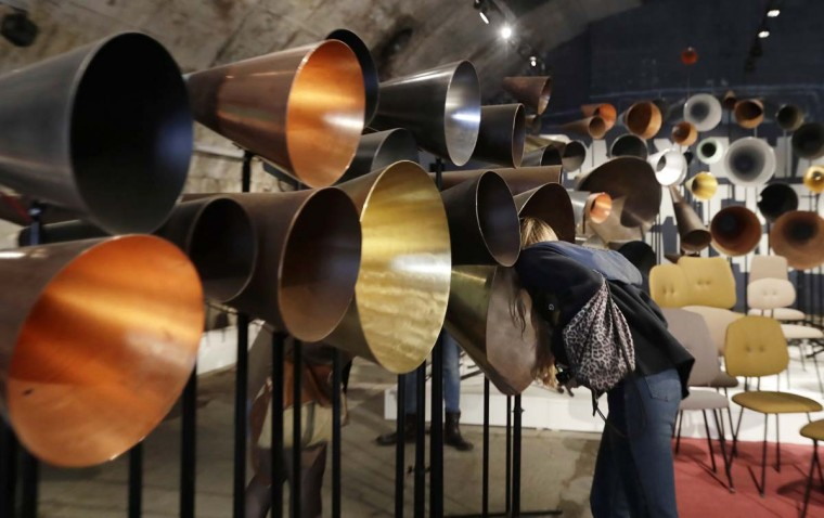 A woman looks closely at creations by Maarten Baas' furniture designers, part of the Design Fair exhibition in Milan, Italy, Thursday, April 6, 2017. (AP Photo/Antonio Calanni)