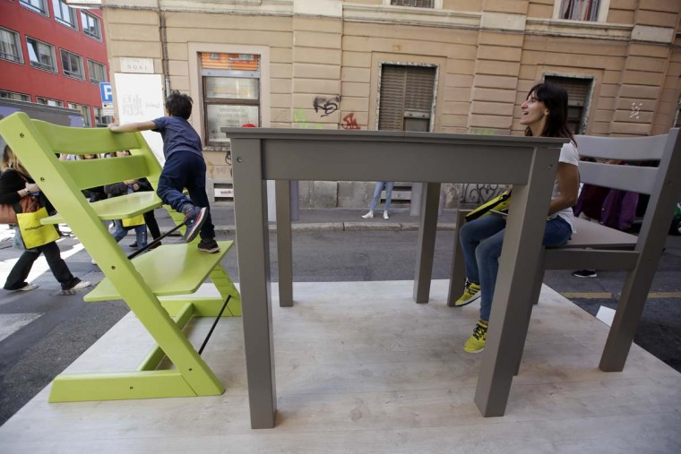 A woman jokes with her son sitting on big chairs by 'Casa Stokke' design company, part of the Design Fair exhibition, in Milan, Italy, Thursday, April 6, 2017. (AP Photo/Luca Bruno)