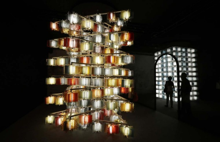 """People looks an installation called """"Strata"""" by Salviati's furniture designers, part of the Design Fair exhibition in Milan, Italy, Thursday, April 6, 2017. (AP Photo/Antonio Calanni)"""