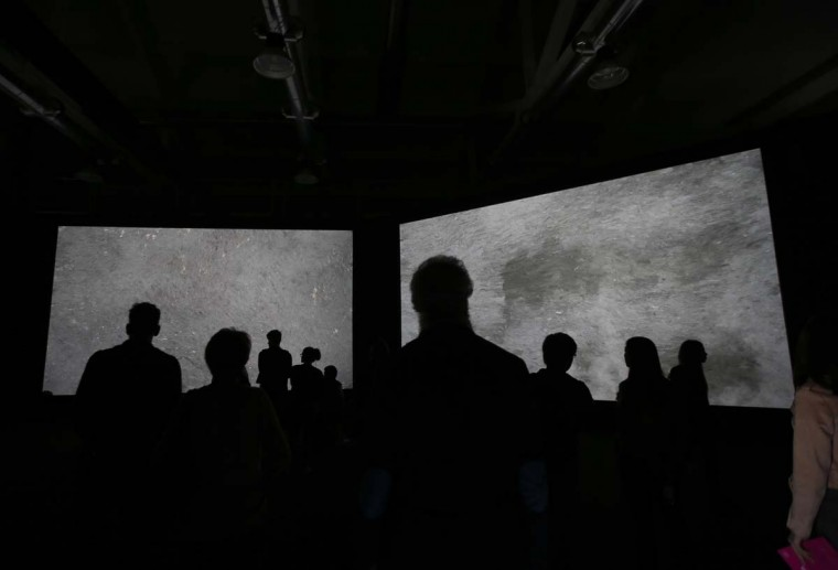 Visitors watch the 'IQOS' project pathfinder visual installation, by artist Quayola, part of the Design Fair exhibition, in Milan, Italy, Thursday, April 6, 2017. (AP Photo/Luca Bruno)