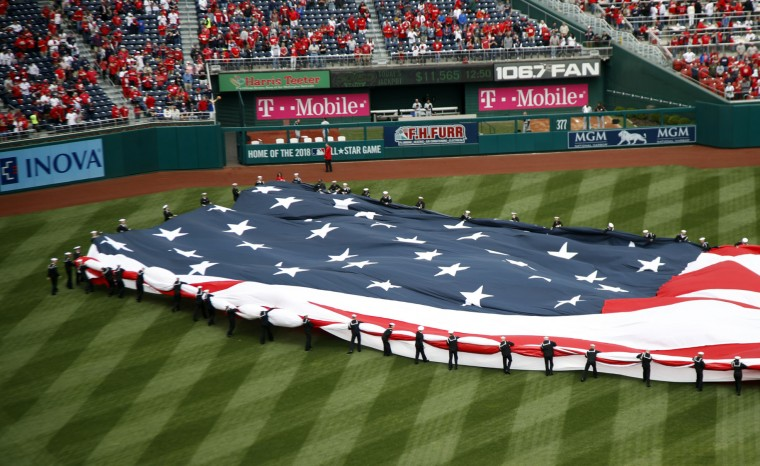 United States Navy sailor gather a giant American flag covering the baseball diamond during the opening day ceremony of a baseball game between the Washington Nationals and Miami Marlins in Washington, Monday, April 3, 2017. (AP Photo/Manuel Balce Ceneta)