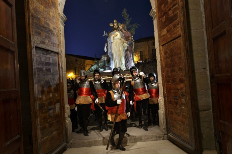 Penitents from the 'Armaos' brotherhood carrying an image representing a story of the Bible take part in a procession in Siguenza, Spain, on Tuesday, April 11, 2017. Hundreds of processions take place throughout Spain during the Easter Holy Week. (AP Photo/Daniel Ochoa de Olza)